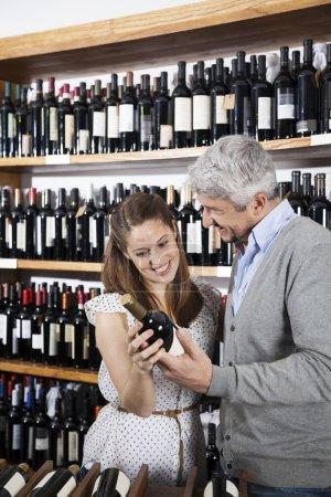 Happy Couple Holding Wine Bottle In Supermarket