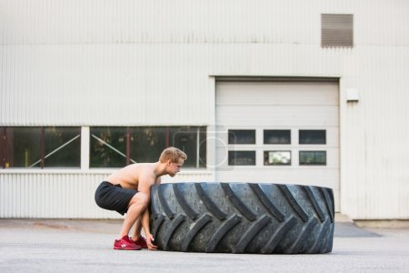 Determined Athlete Lifting Large Tire