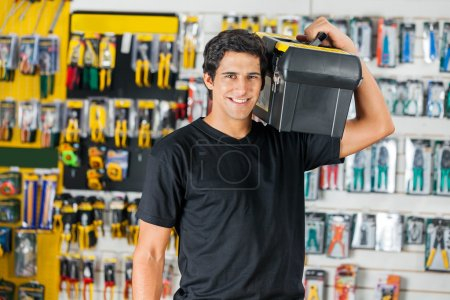 Smiling Man Carrying Toolbox On Shoulder In Store