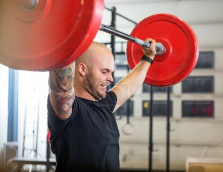 Athlete Exercising With Barbell At Gym