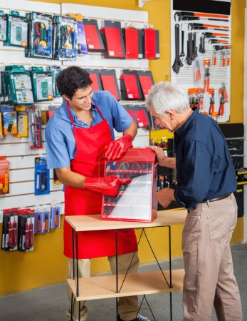 Photo for Young salesman guiding senior man in selecting tools at hardware store - Royalty Free Image