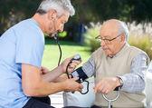 Medico di misurare la pressione arteriosa delluomo anziano