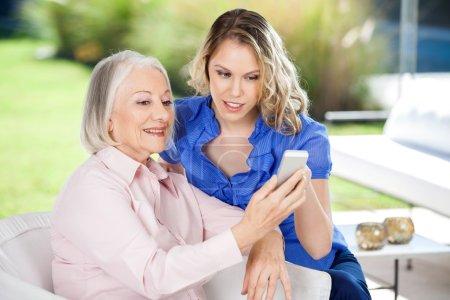 Granddaughter Assisting Granddaughter In Using Smartphone