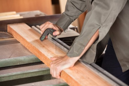 Midsection Of Carpenter Cutting Wood With Tablesaw