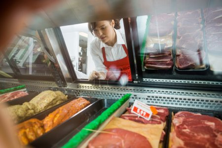 Saleswoman Looking At Variety Of Meat Displayed In Shop