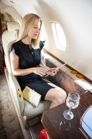 Wealthy Woman Using Tablet Computer In Private Jet