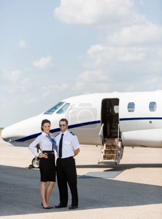 Stewardess And Pilot Standing Together Against Private Jet