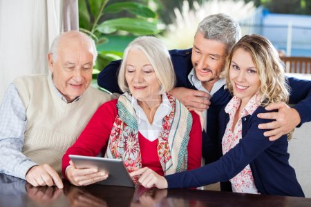Woman Using Digital Tablet With Family At Nursing Home
