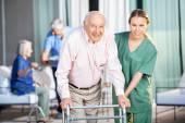 Žena Domovník pomáhá starší muž v používání Zimmer rám