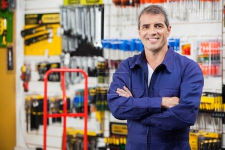 Photo pour Portrait d'un travailleur confiant les bras croisés debout dans une quincaillerie - image libre de droit