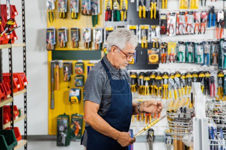 Photo for Side view of senior man working in hardware shop - Royalty Free Image
