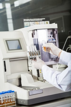 Photo for Cropped image of male researcher examining samples by urine analyzer in lab - Royalty Free Image