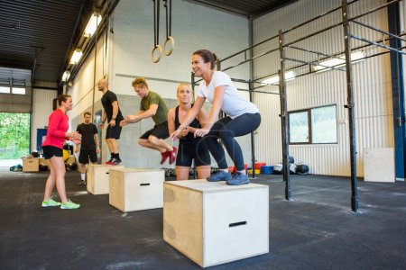 Photo for Male and female athletes doing box jumps at gym - Royalty Free Image