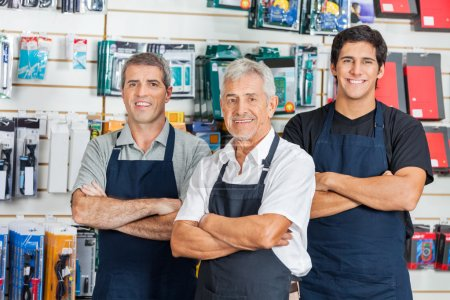 Photo for Portrait of happy salesmen standing arms crossed in hardware store - Royalty Free Image