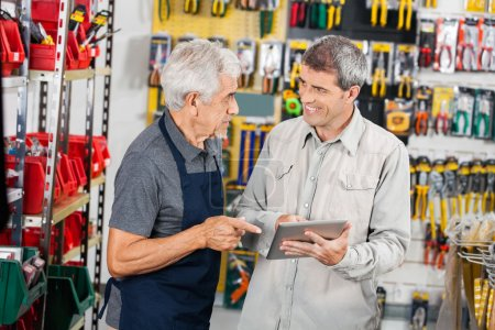 Photo for Senior salesman with male customer using digital tablet in hardware store - Royalty Free Image