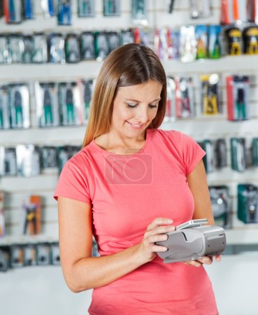Woman Making Payment Through Smartphone In Hardware Store