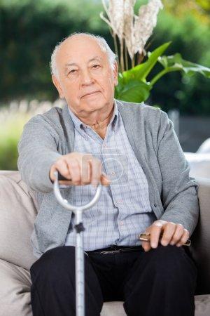 Portrait Of Elderly Man Holding Metal Walking Stick