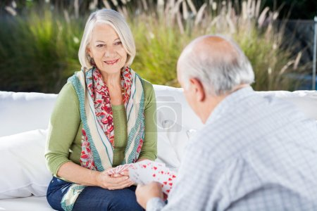 Photo for Happy senior woman playing cards with man at nursing home porch - Royalty Free Image