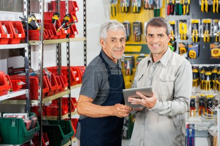 Photo for Portrait of salesman and customer using tablet computer in hardware store - Royalty Free Image