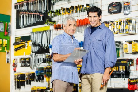 Photo for Portrait of happy father and son with clipboard in hardware store - Royalty Free Image