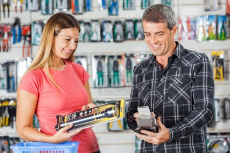Couple Paying For Flashlight Through Smartphone In Store