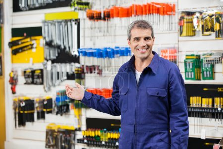 Photo for Portrait of smiling worker in overalls gesturing in hardware store - Royalty Free Image