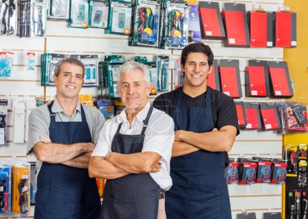 Photo for Portrait of smiling salesmen standing arms crossed in hardware shop - Royalty Free Image