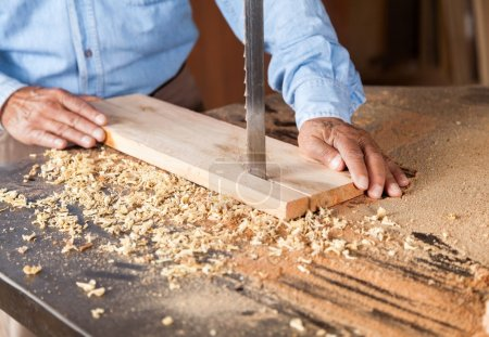 Photo for Cropped image of senior carpenter cutting wood with bandsaw in workshop - Royalty Free Image