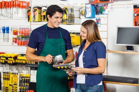 Photo pour Femme heureuse tenant tournevis ensemble avec travailleur balayant carte de crédit à la quincaillerie - image libre de droit