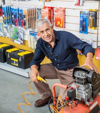Photo pour Portrait de pleine longueur de confiance homme senior avec compresseur d'air en quincaillerie - image libre de droit