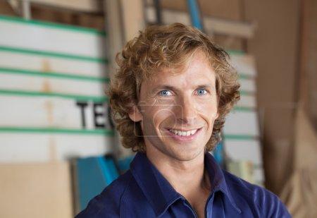 Confident Carpenter Smiling In Workshop