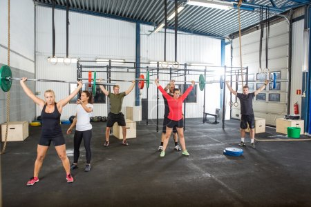 Instructor Assisting Athletes In Lifting Barbells