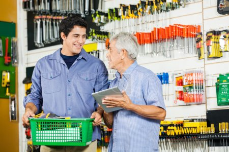 Photo for Father and son with basket and digital tablet in hardware store - Royalty Free Image