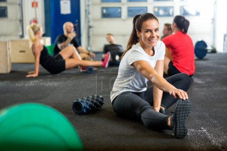 Photo for Portrait of happy young woman doing stretching exercise at cross training box - Royalty Free Image