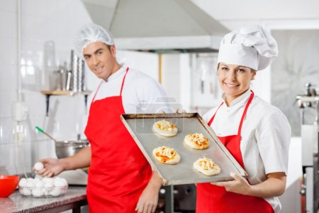 Smiling Chef Holding Pizzas On Tray With Colleague In Background