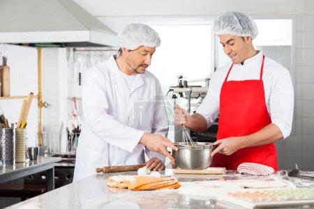 Photo pour Chefs masculins discuter lors de la préparation des pâtes ravioli au comptoir de la cuisine commerciale - image libre de droit