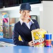 Portrait of smiling worker with popcorn bucket and...