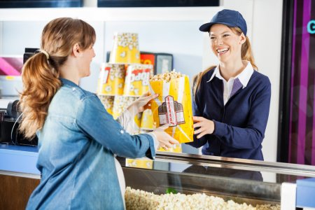 Happy Seller Giving Popcorn To Pregnant Woman At Concession Stan
