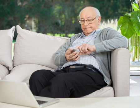 Senior Man Text Messaging Through Smartphone At Porch