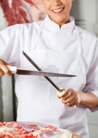 Midsection Of Female Butcher Sharpening Knife