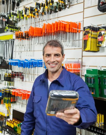 Photo for Portrait of confident worker offering packed product in hardware store - Royalty Free Image
