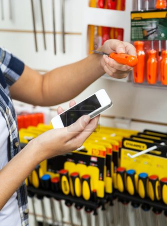 Photo for Cropped image of female customer holding cellphone and screwdriver in hardware store - Royalty Free Image