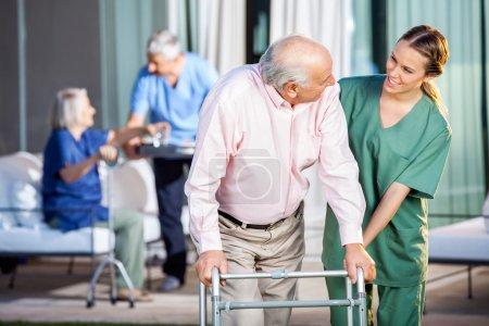 Photo pour Gardienne heureuse aidant l'homme âgé à utiliser Zimmer cadre à la maison de soins infirmiers cour - image libre de droit