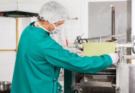 Chef Adjusting Pasta Sheet In Machine