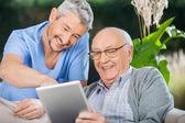 Infermiera e Senior uomo che gode mentre utilizzando Tablet Computer