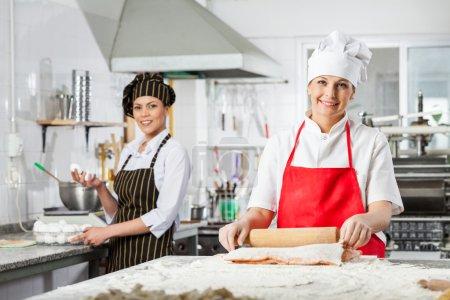 Happy Female Chefs Preparing Pasta In Kitchen