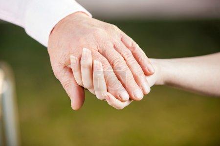 Nurse Holding Senior Mans Hand