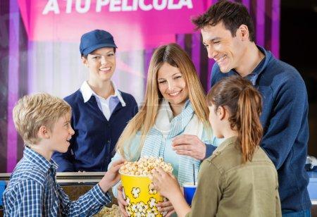 Happy Family Enjoying Popcorn At Cinema Concession Counter