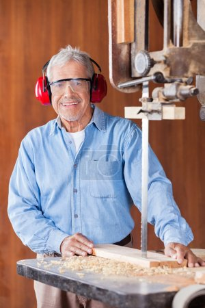 Happy Carpenter Cutting Wood With Bandsaw