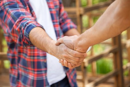 Photo pour Image recadrée de travailleurs de la construction serrant la main dans la cabine sur le site - image libre de droit